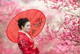 Fototapeta Asian style portrait of a woman with red umbrella